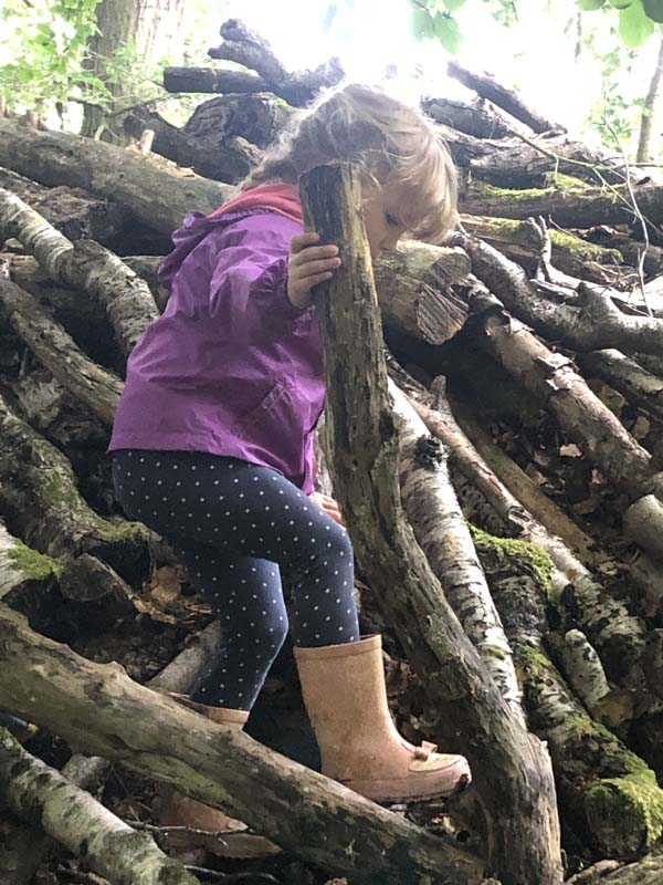Girl climbing on logs