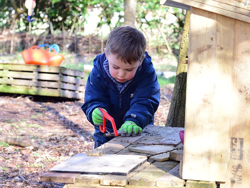 Forest School - Boy sawing wood
